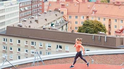 A woman runs at a rooftop running track.